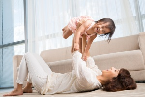 Chinese young lady playing with her daughter at home