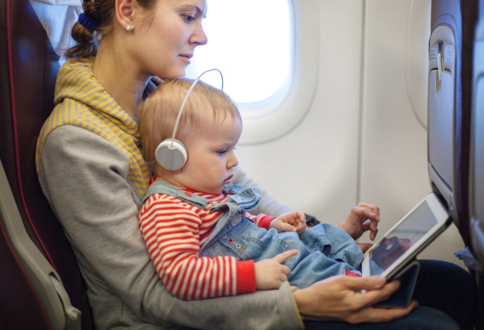 mother and toddler son using tablet pc while on board
