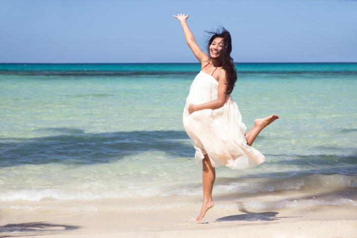 pregnant woman jumping on the beach