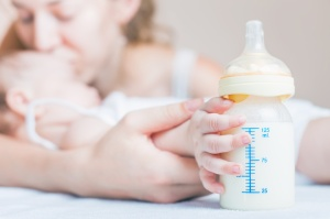 Baby holding a baby bottle with breast milk for breastfeeding. Mothers breast milk is the most healthy food for newborn baby.